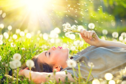 Beautiful young woman lying on the field in green grass and blowing dandelion