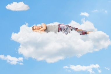 Tranquil scene of a woman sleeping on cloud