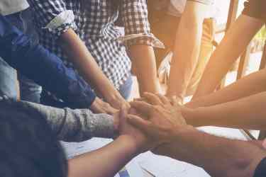 Business people join hand together during their meeting