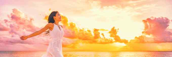Well being free woman with open arms in the air blissful happiness concept banner. Happy woman against pink pastel colorful sunset sky.