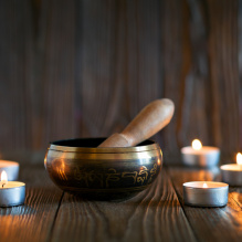 singing bowl on dark wooden background. Burning candles and oil for aromatherapy and massage..